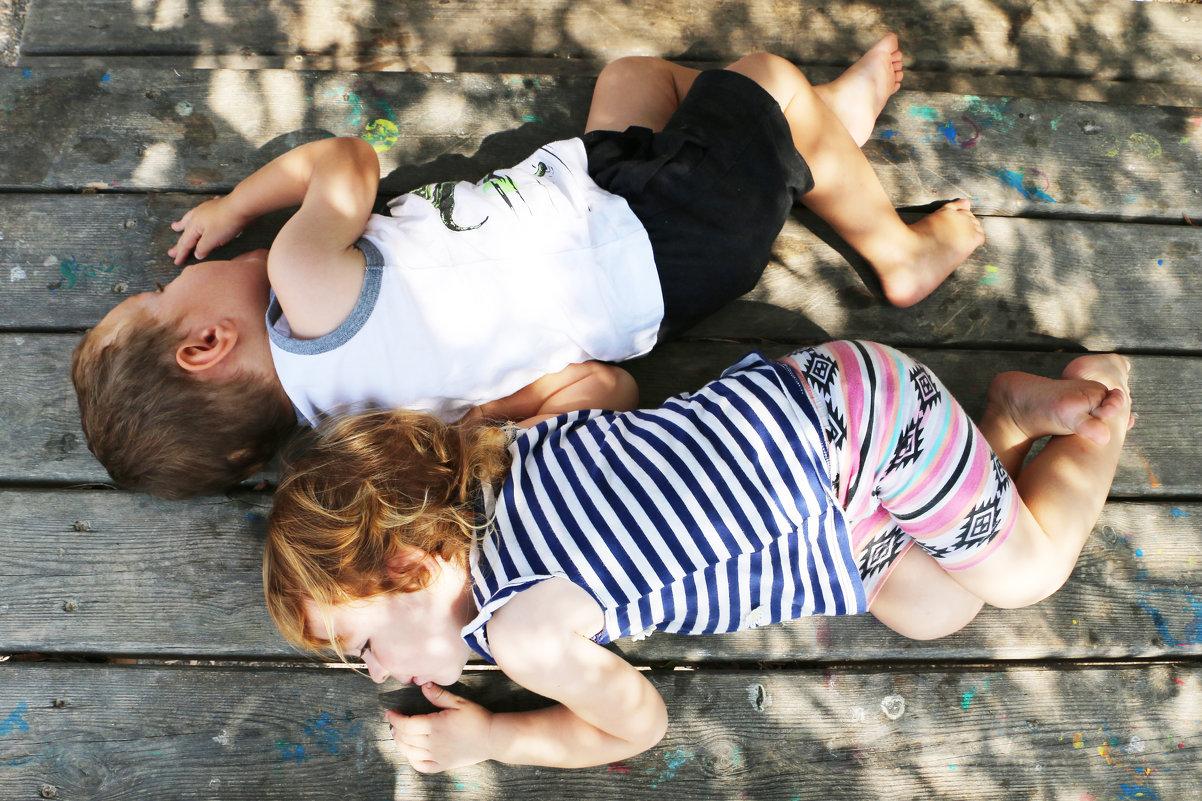 Уставшие дети отдыхают на деревянном столе в парке - Oleg Kolesnikov