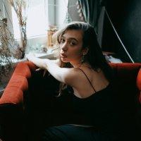 Девушка в классическом черном платье строго смотрит в камеру, сидя на красном бархатном диване :: Lenar Abdrakhmanov