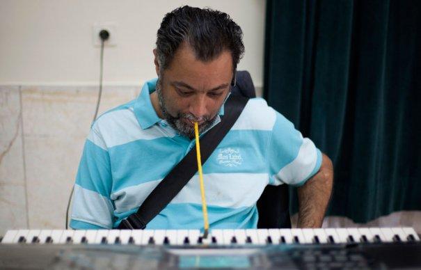 """Шахрам Кодайе проводит """"музыкальную"""" терапию в доме для инвалидов, фото: Morteza Nikoubazl"""