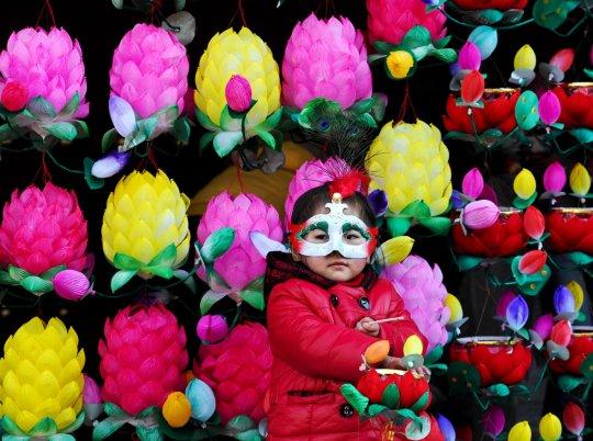 Девочка в маске для фестиваля около стены из лотосов