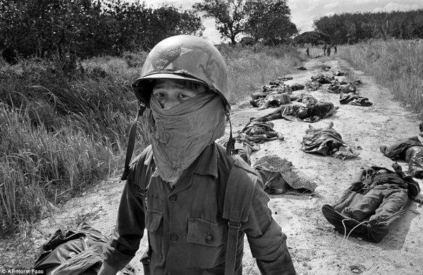 Вьетнамский санитар обходит тела американцев и солдат южно-вьетнамской армии, убитых в боевых действиях против Вьетконга в 45 милях к северо-востоку от Сайгона, в ноябре 1965 года