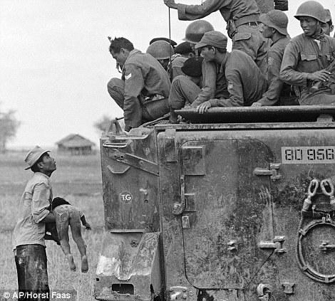 Отец держит тело своего ребенка перед солдатами Южно-вьетнамской армии