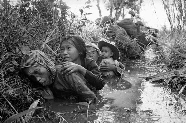 Фотографиия Хорнста Фааса,  на которой женщина и дети прячутся в канаве во время битв близ Сайгона в 1966 г
