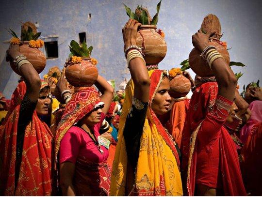 Девушки несут кокосы в кувшинах