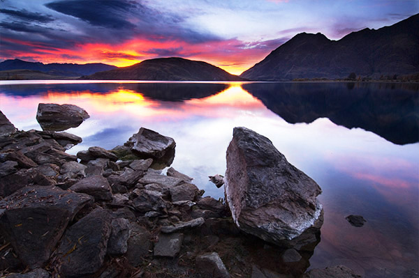 Озеро Ванака, Новая Зеландия. Для того чтобы получить эту фотографию, пришлось лечь на землю. Обратите внимание на то, как большой камень на переднем плане повторяет форму гор, отраженных в  воде.