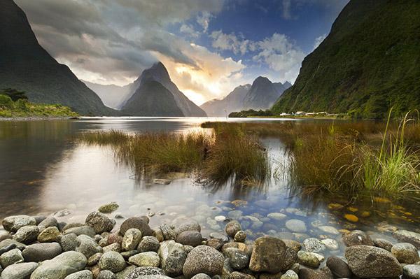 Милфорд Саунд, Новая Зеландия. Главным в этой фотографии является драматичный свет, играющий в облаках над горным пиком, элемнты же среднего и ближнего плана являются критически важной поддержкой основной темы и всей композиции.