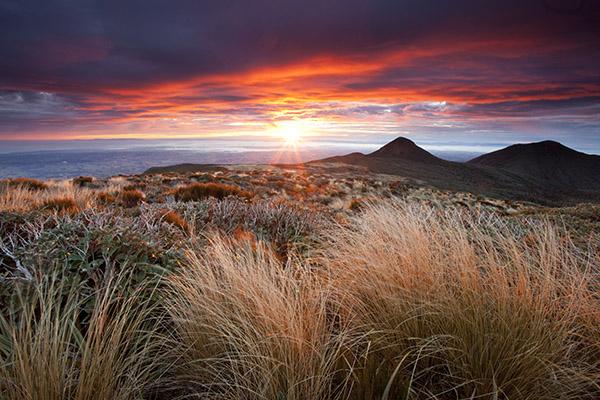 Эгмонт, Новая Зеландия. Обратите внимание на таинственные темные холмы, контрастирующие с теплыми тонами рассвета на остальной части пейзажа.