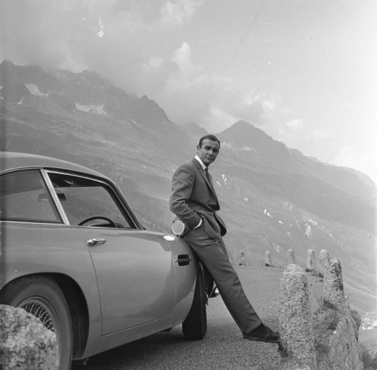 . SEAN CONNERY relaxes on the bumper of his Aston Martin DB5 during the filming of location scenes for 'Goldfinger' in the Swiss Alps. Copyright Notice - © 1964 Danjaq, LLC and United Artists Corporation. All rights reserved.
